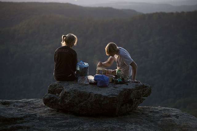 Hikers Andrew Newcomb 402-707-0783, and  Para Somer of Lincoln Nebraska prepare dinner and Andrew plays harmonica at dusk and under moonlight with a view of the Ozarks from White Rock Mountain, Ozark Highlands Trial, Arkansas. They are hiking part of the Ozark Highlads Trail.